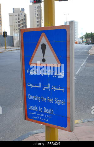 Road sign in English and Arabic in Kuwait City, Crossing the red signal leads to death. - Stock Photo