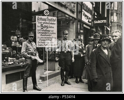 """Vintage B&W anti-Jewish racist inflammatory image of SA Sturmabteilung or """"Brownshirts"""" storm detachment members calling for the boycott of Jewish shops in Friedrichstraße, Berlin; April 1, 1933. The sign with Nazi swastika emblem says: """"Germans, Attention! This shop is owned by Jews. Jews damage the German economy and pay their German employees starvation wages. The main owner is the Jew Nathan  Schmidt."""" - Stock Photo"""