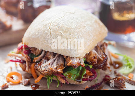Pulled pork bun with lettuce and barbecue sauce - Stock Photo