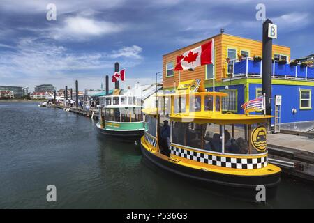 Tourists and Water Taxi Boats in Fisherman's Wharf near Victoria City Center Inner Harbor on Vancouver Island, British Columbia Canada - Stock Photo