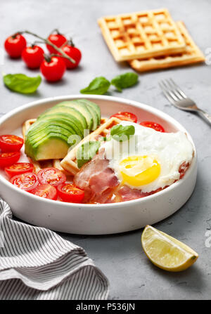 healthy breakfast. Belgian waffles with avocado, bacon and fried egg in a white plate on a gray concrete background. - Stock Photo