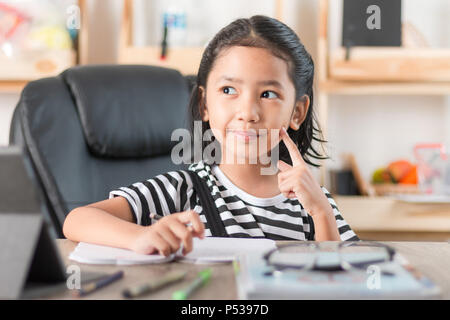 Asian little girl doing homework on wooden table select focus shallow depth of field - Stock Photo