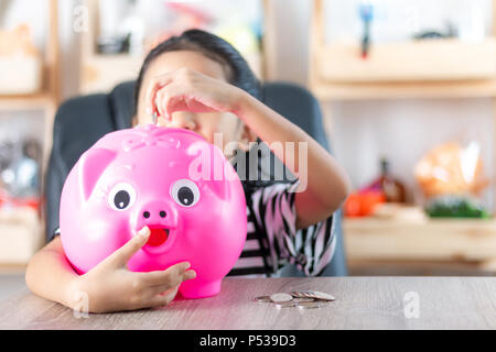 Asian little girl in putting coin in to piggy bank shallow depth of field select focus at the pig - Stock Photo
