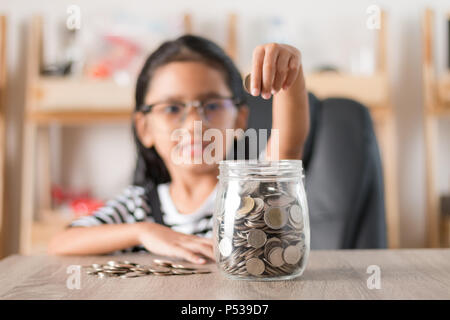 Asian little girl in putting coin in to glass jar shallow depth of field select focus at the jar - Stock Photo