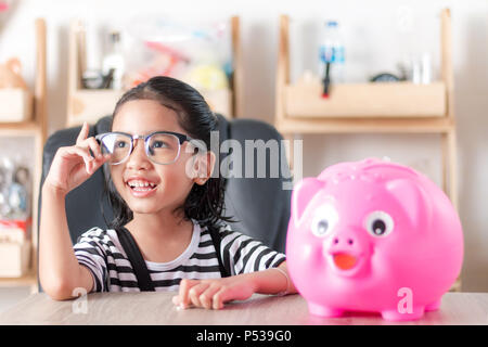 Asian little girl smiling with piggy bank shallow depth of field select focus at the face - Stock Photo