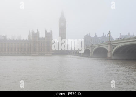 The Palace of Westminster (or Houses of Parliament) with Big Ben sit in the fog on the north bank of the River Thames in London - Stock Photo