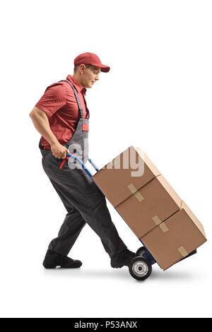 Full length profile shot of a mover with a hand truck loaded with cardboard boxes isolated on white background - Stock Photo