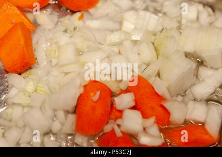 Onions and carrots are cooked in a skillet. - Stock Photo