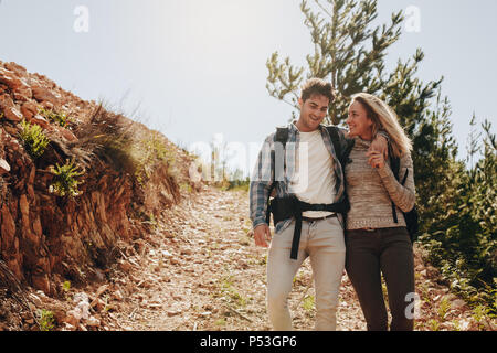 Loving young couple walking down the mountain trail and smiling. Caucasian couple having fun on hiking day. - Stock Photo
