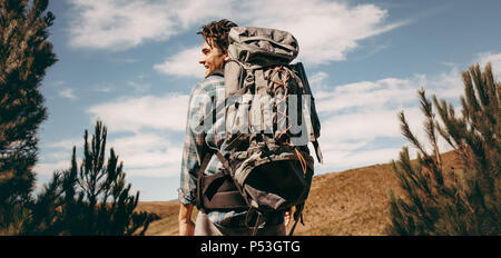 Rear view shot of happy young man with backpack going on a camping. Caucasian male hiker on mountain looking away and smiling. - Stock Photo