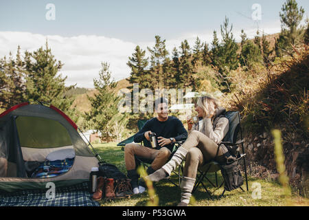 Man and woman sitting in chairs outside the tent having coffee and talking. Couple camping in forest. - Stock Photo
