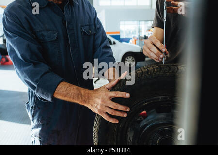 Two technicians checking the depth of tire tread with measuring instrument. Mechanics inspecting the tire in workshop. Closeup shot with focus on hand - Stock Photo
