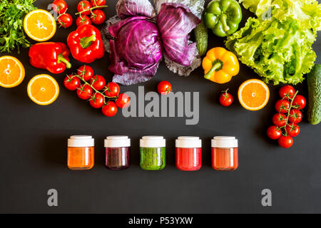Fresh colorful organic vegetables and set of homemade different drinks on a black background. - Stock Photo