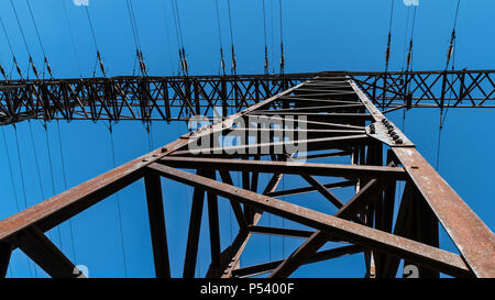 Transmission tower close-up against blue sky. Silhouette of tall rusty electricity pylon of power line. Frog's perspective. Energy supply, environment. - Stock Photo