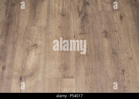 Modern vinyl floor with old wood imitation. Close-up of new beige flooring with texture from tiles with brown grains and knots. Decorative background. - Stock Photo