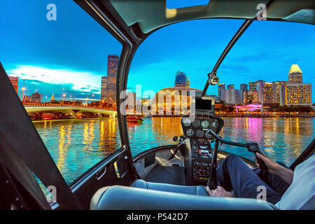 Helicopter cockpit interior flying on Skyline of Singapore in marina bay with cruise boats in the harbor at blue hour. Night scene waterfront in Singapore bay. - Stock Photo