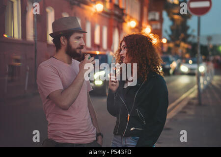 Loving couple of hipsters on date. Guy in hat and T-shirt is holding electronic cigarette. Girl with curly red hair is holding an e-cigarette. They ar - Stock Photo