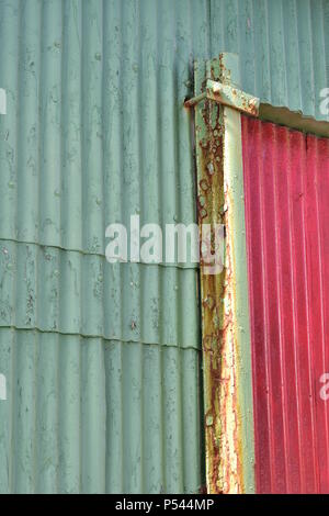 Pale green and red exterior wall made from corrugated sheet metal with some patches of rust. - Stock Photo