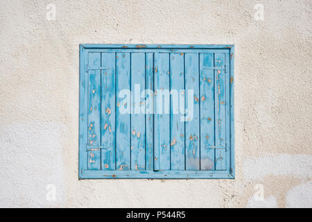 Cyprus, Larnaca. Blue wooden, peeled window, shutters on pink wall. Facade of old stone building, closeup. - Stock Photo
