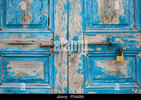Wooden peeled blue door, locked, aged for backdrop. Old entrance with rusty latch and padlock. Closeup. - Stock Photo