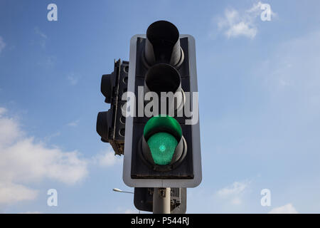 Green traffic light isolated. Signal that it is safe to go on the way. Blue sky with few clouds background. Close up under view. - Stock Photo