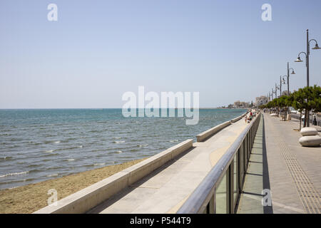 Cyprus, Larnaca city. Stone path for promenade around the sea. Harbor, beach, building, blue sky background. - Stock Photo