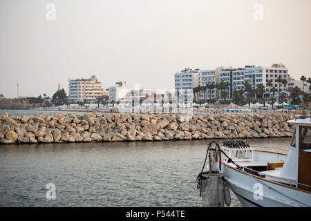 Breakwater of stones at Cyprus, Larnaca. Summer destination. Beach, sea, town, blue sky background. - Stock Photo