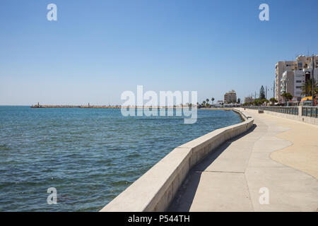 Cyprus, Larnaca city. Stone path around and above the sea. Harbor, beach, buildings, blue sky background. - Stock Photo