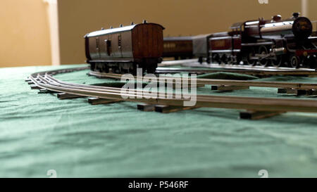 Closeup vintage model electric train formed by a steam locomotive and a green passenger cars running on the rails. - Stock Photo