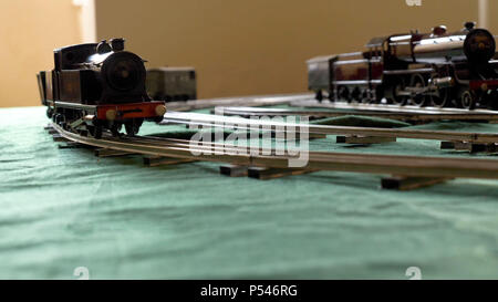 Closeup vintage model electric train formed by a steam locomotive and a green passenger cars running on the rails - Stock Photo