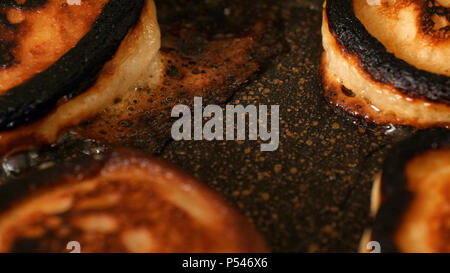 Closeup view burned pancakes frying in bubble vegetable oil on preheat cast iron pan at home. - Stock Photo