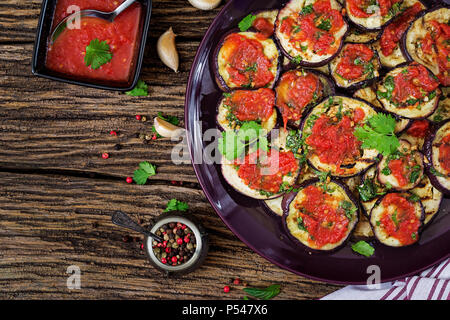 Eggplant grilled with tomato sauce, garlic, cilantro and mint. Vegan food. Grilled aubergine. Top view. Flat lay - Stock Photo