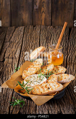 Baked cheese Camembert with rosemary and honey. Tasty food. - Stock Photo