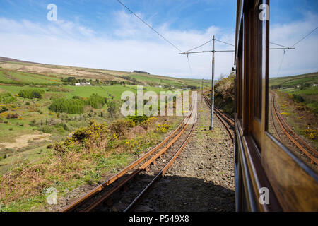View through window from Snaefell Mountain Tramway electric railcar train descending railway tracks on Fell system track built 1895. Laxey Isle of Man - Stock Photo