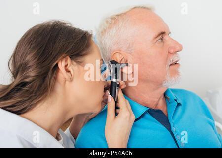 Doctor examining senior man's ear - Stock Photo