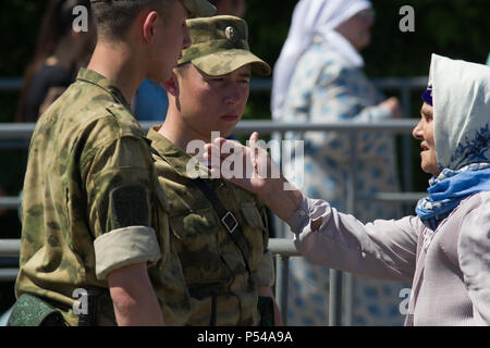 KAZAN, RUSSIA - JUNE 23, 2018: Traditional Tatar festival Sabantuy - Cute old woman in a scarf talking to young soldiers - Stock Photo