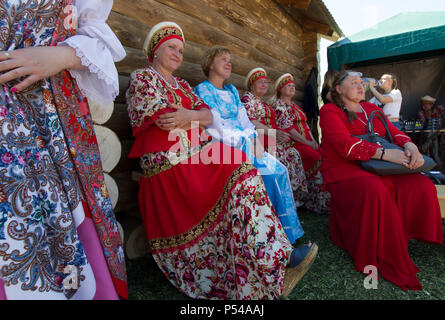 KAZAN, RUSSIA - JUNE 23, 2018: Traditional Tatar festival Sabantuy - Mature women artists in russian national dresses sitting on the bench - Stock Photo