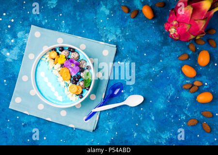 Smoothie bowl with fruits, berries, nuts and flowers. Tropical healthy smoothie dessert. Healthy breakfast, vegetarian, dieting concept. Top view, fla - Stock Photo
