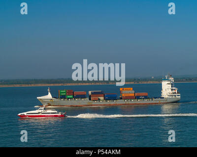 Red Funnel catamaran ferry Red Jet 3 passing container ship X-press Mulhacen in Southampton Water, England, - Stock Photo