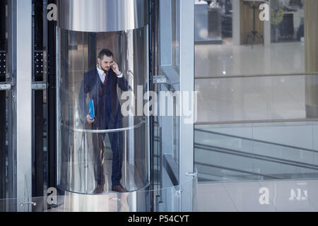 Businessman in modern glass elevator talking by the phone and holding papers - Stock Photo