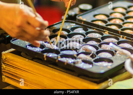 Vendor is cooking for Khanom khrok or coconut-rice pancakes, one of the ancient Thai desserts. - Stock Photo