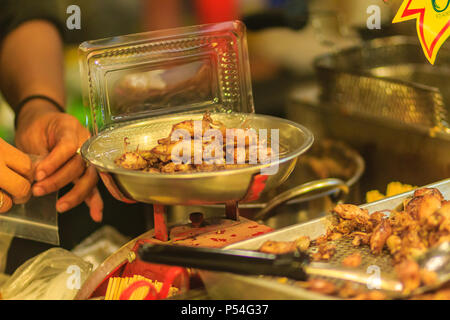 Vendor is selling fried baby squid with garlic in night market at Bangkok, Thailand. - Stock Photo