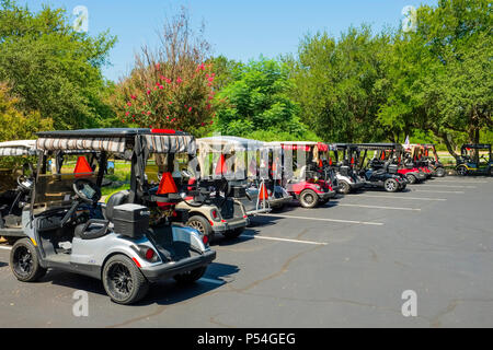 Battery powered electric golf carts await golfers in Sun City Texas adult senior retirement community golf course parking lot - Stock Photo