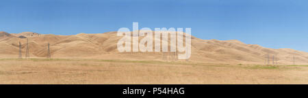 Panoramic landscape of Central California along Interstate 5, dry from drought. Power lines dotting the hillsides. High fire hazard. - Stock Photo