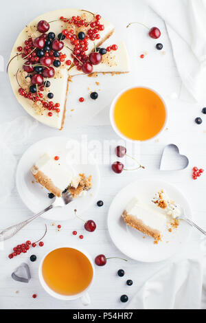 Served table with New York cheesecake with berries on white wooden table. Angle view. - Stock Photo
