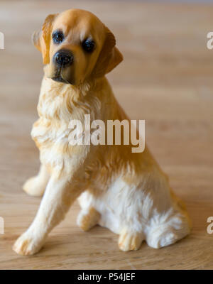 Golden Retriever figurine on a wooden background - Stock Photo