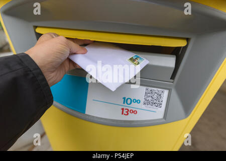 Man posting off a a letter in a post or mail box - Stock Photo