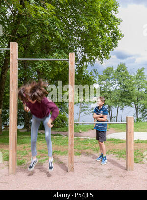 Teenage girl jumping off a crossbar in playpark whilst younger brother watching in awe - Stock Photo