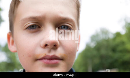 Extreme close up face portrait of blue eye 10 year old young boy looking serious and confident at camera - Stock Photo