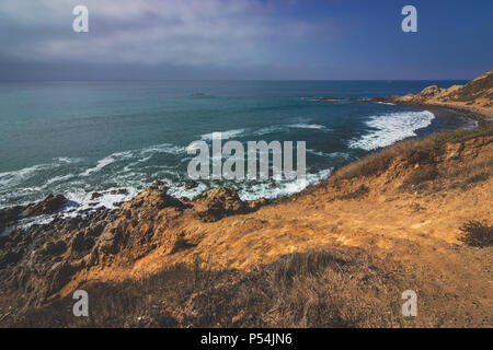 Beautiful waves crashing onto the rocky beach of Bluff Cove with Flat Rock Point rock formation in the background, Palos Verdes Estates, California - Stock Photo